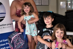 Mom with three smiling children who are holding their new backpacks