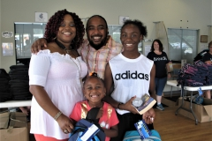 Family poses smiling with their new backpacks