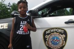 Boy poses next to police car