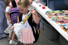 Young girl puts free toothbrush in her bag.