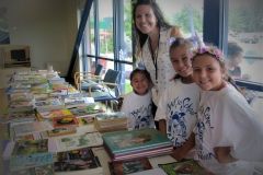 Volunteers pose by the free books table